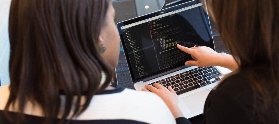 To kvinder kigger på kode på computer