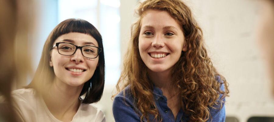 Dame og kvinde smiler til en tredje person